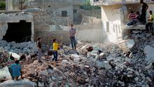 Civilians stand on rubble at a site hit by what activists said was an explosive container dropped by forces loyal to Syria's President Bashar al-Assad in the northern town of Saraqib, near Idlib. Photo: Reuters