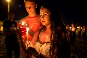 People hold candles as they walk to the beach of the Imperial Marhaba Hotel, where a gunman had carried out an attack, in Sousse, Tunisia, June 28, 2015