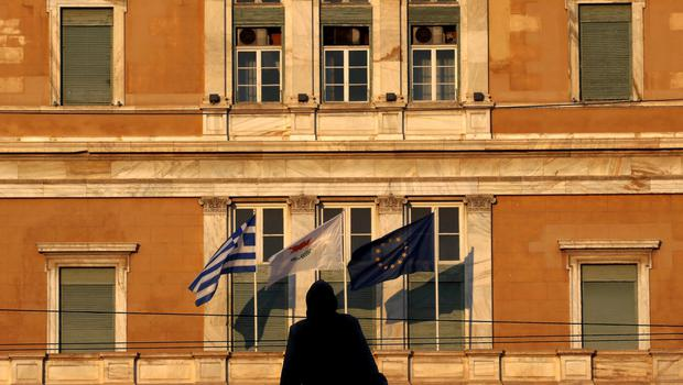 A woman is silhouetted against the parliament where the flags of Greece, Cyprus and the EU are fluttering in Athens, Greece June 24, 2015. Prime Minister Alexis Tsipras flew to Brussels to meet Greece's international creditors on Wednesday to try to bridge gaps on key elements of the proposals made by his left-wing government to shore up state finances in return for vital loans.  REUTERS/Yannis Behrakis