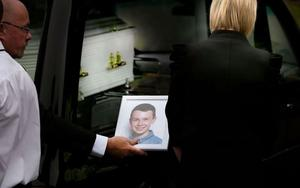 A photograph of Liam Hawe who was murdered along with his siblings and parents in a 'murder suicide'  is passed to his aunt as his remains arrive at their funeral. Gerry Mooney, Independent News & Media