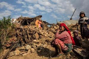 People sit on the rubble of a collapsed building following an earthquake in Kathmandu, Nepal in this Red Cross handout picture taken on April 27, 2015.  REUTERS/IFRC/Palani Mohan/Handout via Reuters