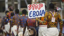 """Actors parade on a street after performing at Anono school, during an awareness campaign against Ebola in Abidjan. The tag on one of the actors read: """"Red card to Ebola"""". Reuters/Luc Gnago"""