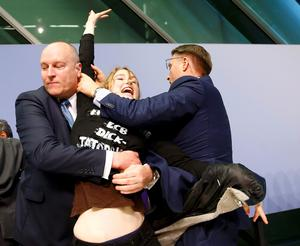 Security officers detain a protester who jumped on the table in front of the European Central Bank President Mario Draghi during a news conference in Frankfurt, April 15, 2015.REUTERS/Kai Pfaffenbach
