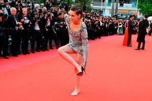 """US actress and member of the Feature Film Jury Kristen Stewart removes her shoes on the red carpet as she arrives on May 14, 2018 for the screening of the film """"BlacKkKlansman"""" at the 71st edition of the Cannes Film Festival in Cannes, southern France.  / AFP PHOTO / Valery HACHEVALERY HACHE/AFP/Getty Images"""