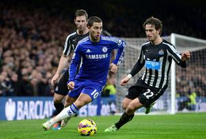 Newcastle United's Mike Williamson (left) and Daryl Janmaat (right) battle for the ball with Chelsea's Eden Hazard