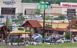 "Law enforcement officers investigate the parking lot of a Twin Peaks restaurant Sunday, May 17, 2015, in Waco, Texas. Waco Police Sgt. W. Patrick Swanton told KWTX-TV there were ""multiple victims"" after gunfire erupted between rival biker gangs at the restaurant. (Rod Aydelotte/Waco Tribune-Herald via AP)"