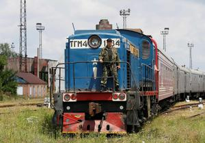 A guard stands on a train carrying the remains of victims of Malaysia Airlines MH17 downed over rebel-held territory in eastern Ukraine after it arrived in the city of Kharkiv, eastern Ukraine