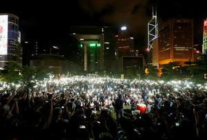 Pro-democracy protesters switch on their mobile phones in an act of defiance in China - but China is a socialist economy.