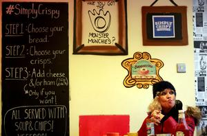A woman sits in the Simply Crispy sandwich cafe in Belfast, northern Ireland January 12, 2015. REUTERS/Cathal McNaughton