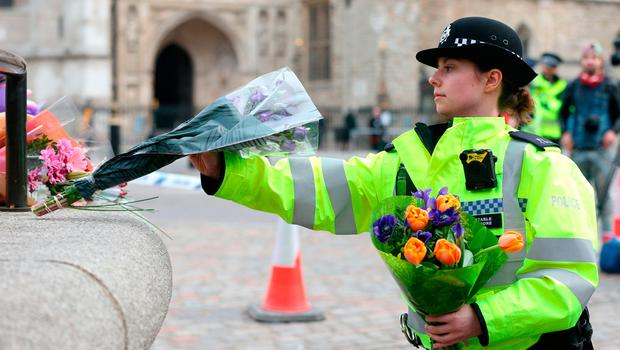 A police officer leaving flowers at the scene of the atrocity. Photo: PA