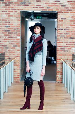 Maria wears  a Grey Knitted Dress, €22, Round Studded Bag, €8, Aztec Scarf, €6 and Burgundy over the Knee Boots, €28 and hat, €10