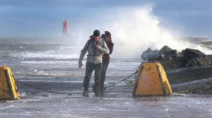 Walkers pictured at the South Bull wall as high winds churn up the sea during high tide.Picture Credit:Frank McGrath 11/1/20