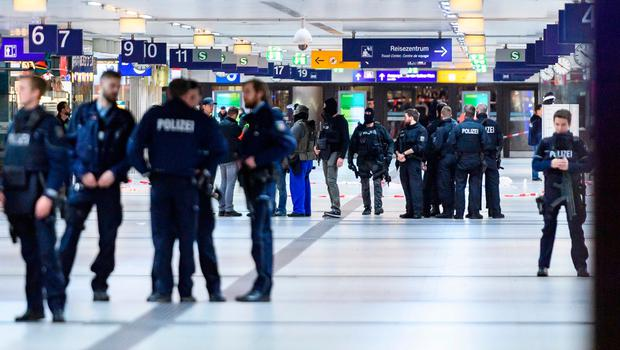 Police and emergency workers stand outside the main railway station following what police described as an axe attack. Photo by Alexander Scheuber/Getty Images