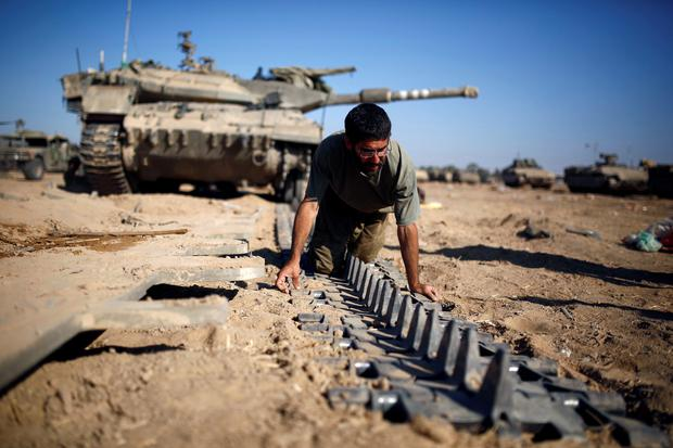 An Israeli reserve soldier checks a tank track near the border with Gaza today