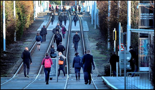 Commuters walk on the Luas line during one of the recent strikes. Photo: Steve Humphreys