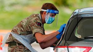 A member of the armed forces takes a swab to test for the novel coronavirus COVID-19 from a visitor to a drive-in testing facility in London. (Photo by Adrian DENNIS / AFP) (Photo by ADRIAN DENNIS/AFP via Getty Images)