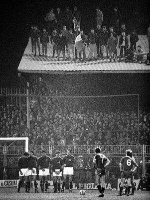 RAISING THE ROOF: Spectators in the terrace and on the roof at Dalymount Park watch as Ireland prepare to take a free-kick against Italy in February 1985. Photo: SPORTSFILE