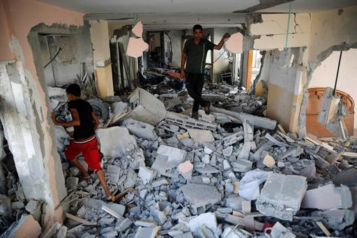 A Palestinian family looks through their damaged home after returning to Beit Hanoun town, which witnesses said was heavily hit by Israeli shelling and air strikes during the Israeli offensive, in the northern Gaza Strip August 5, 2014. REUTERS/Finbarr O'Reilly