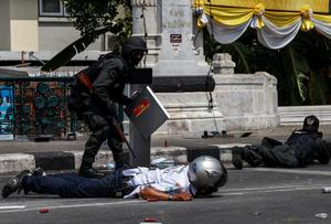 Riot police officers and a rescue worker take cover after an explosion during clashes with anti-government protesters near the Government House in Bangkok