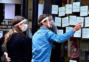 Employees wearing protective face shields and face masks prepare the reopening of a shop in Bordeaux, southwestern France. (Photo by GEORGES GOBET / AFP) (Photo by GEORGES GOBET/AFP via Getty Images)