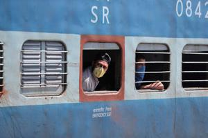 Passengers wearing masks as a precautionary measure against the new virus are seen inside a train in Jammu, India (AP Photo/Channi Anand)