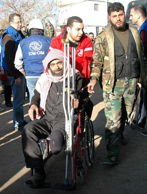 A Syrian Red Crescent worker helps evacuate a man from the besieged district of the central Syrian city of Homs to a safer location on February 9, 2014. A total of 420 people were evacuated from army-besieged districts of the Syrian city of Homs, the province's governor said, as television footage showed exhausted men, women and children. AFP PHOTO/STR        (Photo credit should read -/AFP/Getty Images)