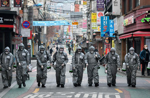 South Korean soldiers wearing protective gear spray disinfectant to help prevent the spread of Covid-19 at a shopping district in Seoul. Photo: Getty Images