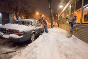An employee of a local restaurant clears his car of snow to make return home as a statewide travel ban goes into effect in New Haven, Connecticut, January 26, 2015.  REUTERS/Michelle McLoughlin