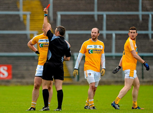 Referee Maurice Deegan issues a red card to Sean McVeigh, Antrim, for a first half incident, as Kieran McGourty and Conor Murray looks on.