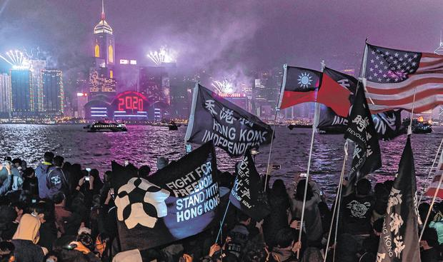 Pro-democracy supporters wave flags and shout slogans during a countdown party in Hong Kong. Photo: Anthony Kwan/Getty Images