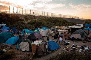 The sun sets behind a make shift camp near the port of Calais on August 2, 2015 in Calais, France