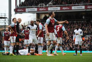 LONDON, ENGLAND - FEBRUARY 01:  Andy Carroll of West Ham United (front) is sent off by referee Howard Webb (3R) after a clash with Chico Flores of Swansea City (grounded) during the Barclays Premier League match between West Ham United and Swansea City at Boleyn Ground on February 1, 2014 in London, England.  (Photo by Steve Bardens/Getty Images)