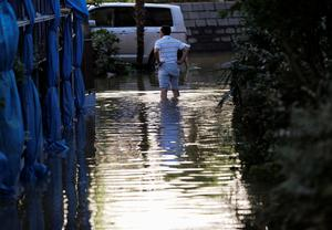 A man stands in a flooded residential area due to Typhoon Hagibis, in Kawasaki, Japan, October 13, 2019. REUTERS/Kim Kyung-Hoon