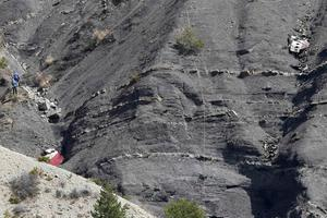 Rescue workers (L) are seen near debris at the crash site of the Germanwings Airbus A320 near Seyne-les-Alpes, French Alps, March 30, 2015. REUTERS/Claude Paris/Pool