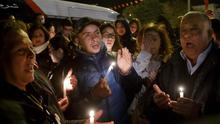 Tunisians holding candles pray at the entrance gate of the National Bardo Museum where scores of people were killed after gunmen staged an attack