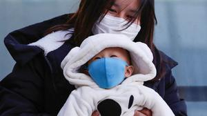 Taking precautions: A mother and her baby wear protective masks in Sapporo, Japan. Photo: Reuters