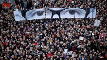 """People hold panels to create the eyes of late Charlie Hebdo editor Stephane Charbonnier, known as """"Charb"""", as hundreds of thousands of French citizens take part in a solidarity march (Marche Republicaine) in the streets of Paris January 11, 2015."""
