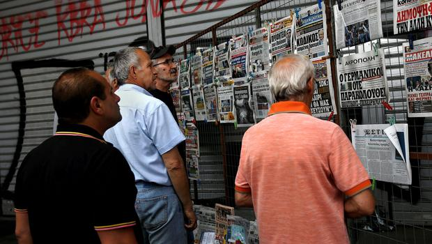 People read newspaper headlines in Athens