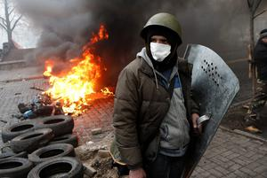 Anti-government protesters man a barricade in central Kiev