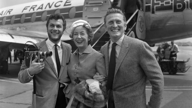 Kirk Douglas and his wife Anne being met by Tony Curtis, (left) on their arrival at London Airport from Paris in 1957. Photo: PA Wire