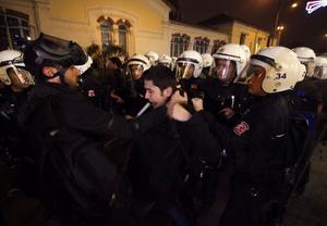 Riot police detain a demonstrator during a protest against a new law tightening control of the Internet in Istanbul
