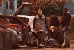 Police investigators search for evidence as an unidentified man is detained (top, 2nd R) during an operation in the eastern French city of Reims, January 8, 2015, after the shooting against the Paris offices of Charlie Hebdo, a satirical newspaper. Police are hunting two French nationals, including brothers Said Kouachi, born in 1980; Cherif Kouachi, born in 1982; and Hamyd Mourad born in 1996, after suspected Islamist gunmen killed 12 people. REUTERS/Christian Hartmann