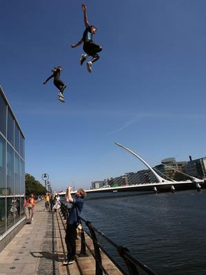 A passerby stops to video young people jumping into the River Liffey on North Wall Quay, Dublin, during the continuing good weather. Photo credit: Brian Lawless/PA Wire