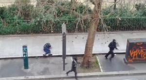 Gunmen flee after shooting a wounded police officer (left) on the ground at point-blank range, outside the offices of French satirical newspaper Charlie Hebdo in Paris, in this still image taken from amateur video shot on January 7. Reuters/Handout via Reuters TV