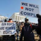 Gun rights advocates hold signs during a rally inside the no-gun zone in front of the Virginia State Capitol building in Richmond, Virginia, U.S. January 20, 2020. REUTERS/Jonathan Drake