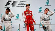 Ferrari driver Sebastian Vettel, center, of Germany celebrates as he stands with Mercedes drivers Nico Rosberg, right, of Germany and Lewis Hamilton of Britain on the podium after winning the Malaysian Formula One Grand Prix at Sepang International Circuit in Sepang