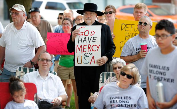 Walden Paige, of Marshalltown, Iowa, center, looks on during a rally to protest the Trump administration's immigration policies, Saturday, June 30, 2018, outside the Marshall County Courthouse in Marshalltown, Iowa. (AP Photo/Charlie Neibergall)