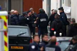 French Prime Minister Manuel Valls (centre) stands near the Paris offices of Charlie Hebdo after a shooting. Reuters/Charles Platiau