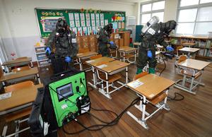 Clean-up time: Military workers disinfect a classroom in Daejeon in South Korea. Photo: Kim Jun-beom/Yonhap via AP