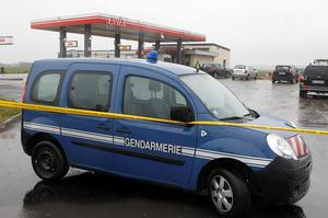 A gendarme car is parked in a gas station in Villers Cotteret, 80 kilometers northeast of Paris, where the suspects were reportedly spotted, Thursday, Jan. 8, 2015,  a day after masked gunmen stormed the offices of a satirical newspaper and killed 12 people. (AP Photo/Michel Spingler)